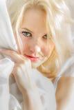 Cara de la mujer joven envuelta en una hoja blanca fotos de archivo