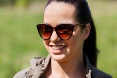 Cara de la mujer joven feliz en gafas de sol al aire libre Fotos de archivo