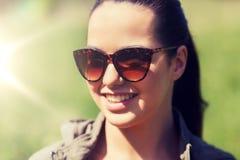 Cara de la mujer joven feliz en gafas de sol al aire libre Imagen de archivo libre de regalías