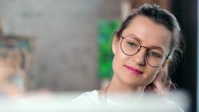 Cara de la mujer positiva adorable del pintor que tiene imagen del dibujo del placer en el primer del taller almacen de metraje de vídeo