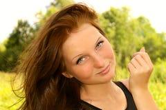 Cara de la mujer que sonríe con el pelo grueso de Brown en al aire libre hermoso del viento Imágenes de archivo libres de regalías