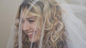 Cara de la novia hermosa joven debajo del velo de novia blanco almacen de metraje de vídeo