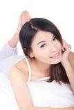 Cara de la sonrisa de la chica joven mientras que miente en cama Imagen de archivo libre de regalías