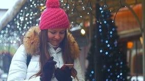 Cara de la sonrisa de la mujer joven en ciudad del invierno Usando el teléfono almacen de metraje de vídeo