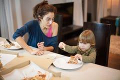 Cara de la sorpresa del niño con un pedazo roto pizza con la madre Imagen de archivo libre de regalías