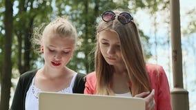 Cara de las estudiantes universitarias hermosas jovenes de las muchachas con el ordenador portátil a disposición en el parque ver almacen de metraje de vídeo