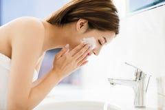 Cara de lavagem da mulher com agua potável no banheiro imagem de stock