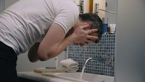 Cara de lavagem do homem da colheita no dissipador vídeos de arquivo