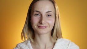 Cara de limpiamiento de la mujer en un fondo amarillo almacen de video