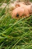 Cara de mentira de la muñeca plástica abajo en la hierba Foto de archivo libre de regalías