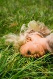 Cara de mentira de la muñeca plástica abajo en la hierba Fotografía de archivo