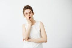 Cara de ocultación agujereada de la muchacha bonita joven cansada detrás de la mano que mira la cámara sobre el fondo blanco Imagen de archivo libre de regalías