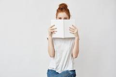 Cara de ocultación de la muchacha astuta hermosa detrás del libro que mira la cámara Fotos de archivo libres de regalías