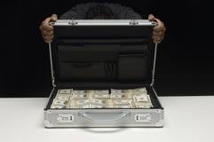 Cara de ocultación de la mujer detrás de la maleta por completo de dólares Imagen de archivo libre de regalías