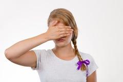 Cara de ocultación del adolescente tímido detrás de la mano Imagenes de archivo