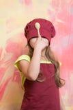 Cara de ocultación del cocinero de la muchacha con el sombrero del cocinero y la cuchara de madera Foto de archivo libre de regalías