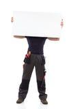 Cara de ocultación del trabajador detrás de un baner Imagen de archivo
