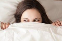 Cara de ocultación juguetona de la mujer joven debajo de la manta, mirando a escondidas de duve Fotos de archivo