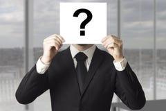 Cara de ocultación del hombre de negocios detrás del signo de interrogación de la muestra Imagenes de archivo