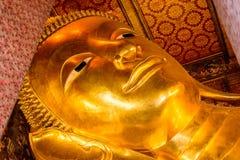A cara de reclinação da estátua do ouro da Buda em Banguecoque, Tailândia Imagem de Stock Royalty Free