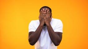 Cara de recubrimiento masculina negra asustada por las manos, sintiendo asustadas, reacción de la tensión foto de archivo libre de regalías