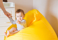 Cara de risa adorable hermosa del niño del bebé El niño sonriente se sienta en una silla Imagen de archivo libre de regalías
