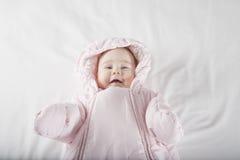 Cara de sorriso do bebê envolvida no snowsuit cor-de-rosa Imagens de Stock Royalty Free