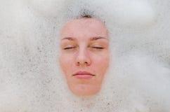 A cara de uma menina bonita nova em um banho branco entre bolhas de sabão do gel do banho da espuma, despida com cabelo molhado,  Fotografia de Stock