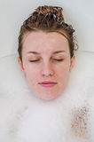 A cara de uma menina bonita nova em um banho branco entre bolhas de sabão do gel do banho da espuma, despida com cabelo molhado,  Imagens de Stock