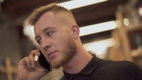Cara de un individuo barbudo hermoso que habla en el teléfono móvil Retrato de un individuo que habla en el móvil almacen de video