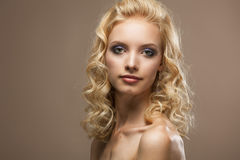 Cara de un pelo rubio rizado hermoso de la mujer joven foto de archivo