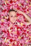 Cara de una chica joven entre los pétalos color de rosa en baño Balneario, salud o fotos de archivo