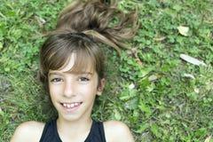 Cara de una muchacha que miente en la hierba Fotografía de archivo libre de regalías