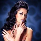 Cara de una mujer atractiva con los clavos azules Imagenes de archivo