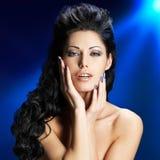 Cara de una mujer atractiva con los clavos azules Foto de archivo libre de regalías