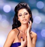 Cara de una mujer atractiva con los clavos azules Imagen de archivo libre de regalías