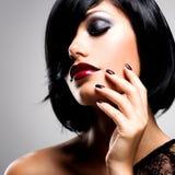 Cara de una mujer con los clavos oscuros hermosos y los labios rojos atractivos Foto de archivo libre de regalías