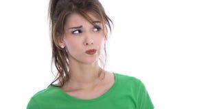 Cara de una mujer joven escéptica en la camisa verde aislada Imagen de archivo libre de regalías