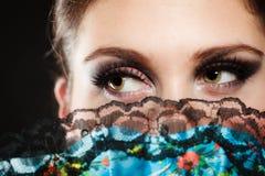 Cara del bailarín del flamenco de la muchacha ocultado detrás de fan Imágenes de archivo libres de regalías
