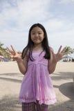 Cara del finger asiático de la demostración de la muchacha que actúa como simbólico del número Fotografía de archivo libre de regalías