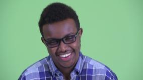 Cara del hombre africano joven feliz del inconformista con las lentes que sonríe y que ríe almacen de metraje de vídeo