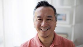 Cara del hombre asiático sonriente feliz en casa almacen de metraje de vídeo