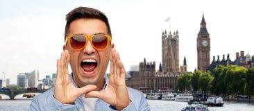 Cara del hombre de grito enojado en camisa y gafas de sol Foto de archivo libre de regalías