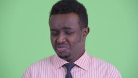Cara del hombre de negocios africano joven subrayado que parece triste y del griterío almacen de metraje de vídeo