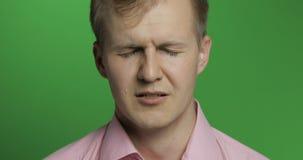 Cara del hombre deprimido joven que llora en el fondo dominante de la croma verde foto de archivo