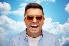 Cara del hombre enojado en camisa y gafas de sol Imagen de archivo