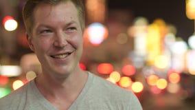 Cara del hombre turístico feliz joven que piensa en las calles de Chinatown en la noche metrajes