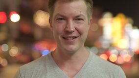 Cara del hombre turístico feliz joven que sonríe contra la vista de las calles en Chinatown en la noche metrajes