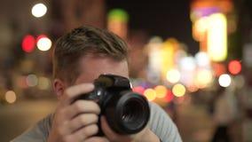 Cara del hombre turístico joven que fotografía contra la vista de las calles en Chinatown en la noche almacen de video