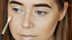 Cara del maquillaje El artista de maquillaje de la muchacha trata el polvo de cara Imágenes de archivo libres de regalías